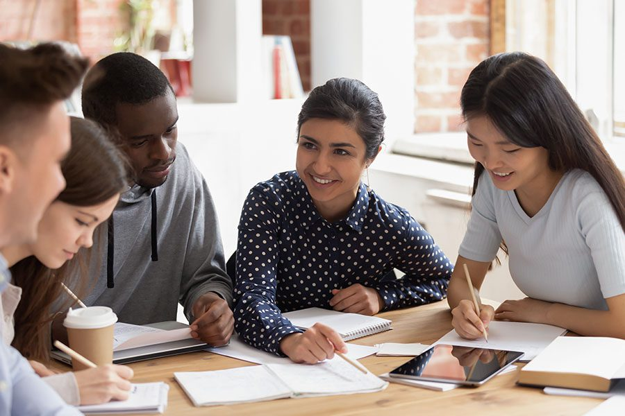 Specialized Business Insurance - Students Sitting At a Desk Studying Together