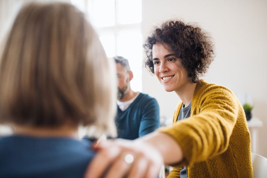 Employee Assistance Plan - Woman Comforting a Fellow Member in Group Therapy