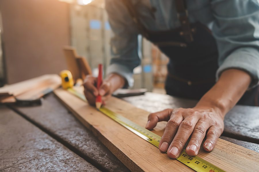 Carpenter Insurance - Carpenter Working With Equipment on Wooden Table in Workshop