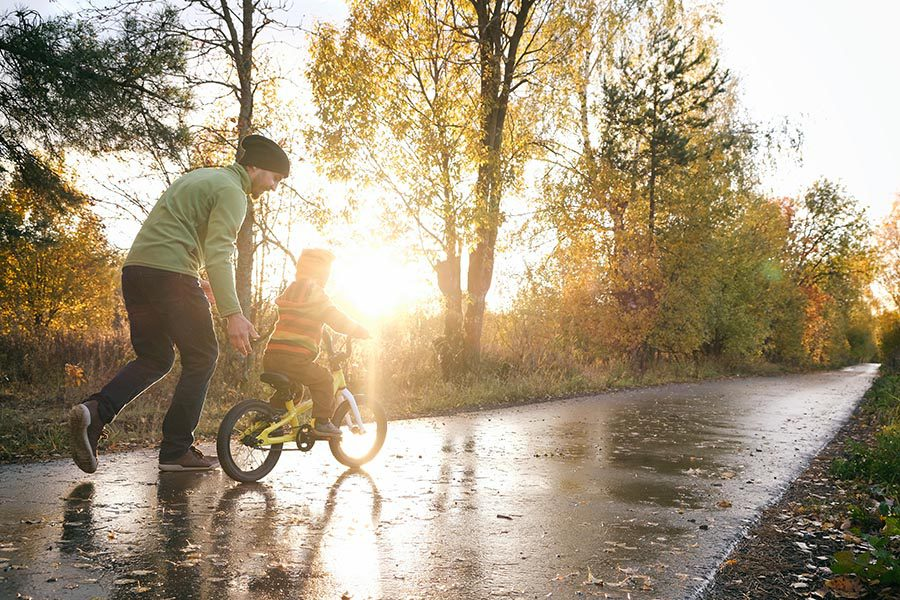About Our Agency - Father and Young Son on a Wet Path in a Park, Father Teaching the Son How to Ride a Bike
