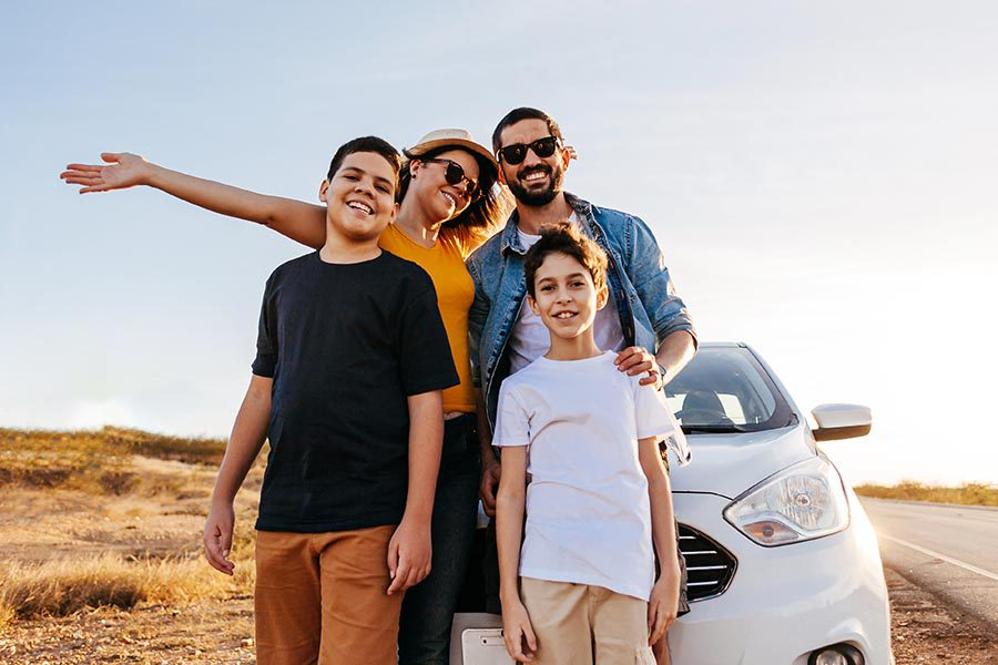 Client Center - Young Family Standing in Front of Their White Car on a Long Country Lane