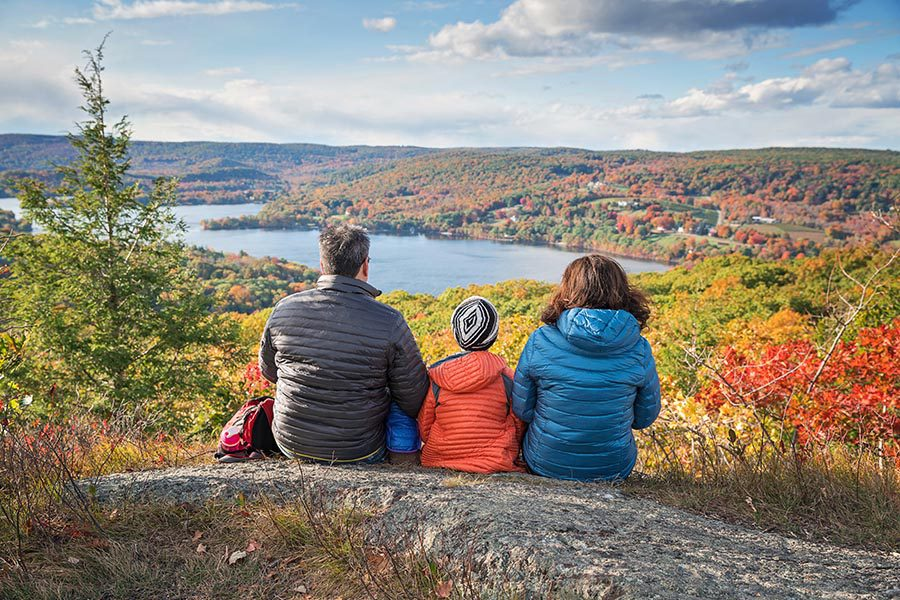 Contact - Mother, Father and Child Wearing Coats, Sitting On a Rocky Ledge Overlooking a New England Landscape