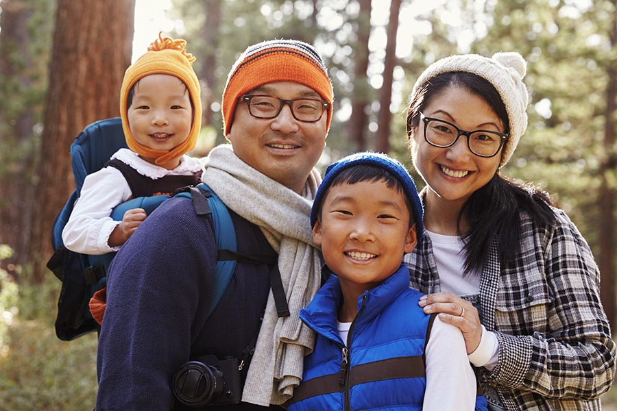 Personal Insurance - Father, Mother, Young Son, and Toddler Daughter on a Hike in the Fall Among Pine Trees, Daughter in a Hiking Backpack