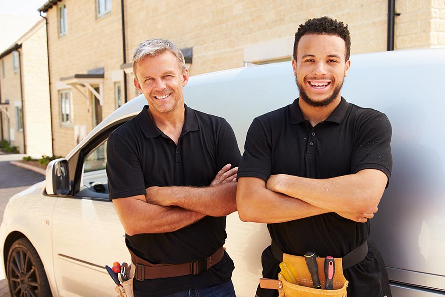 Business Insurance - Contractors Stand by Their Work Van on a Residential Street, Both Smiling