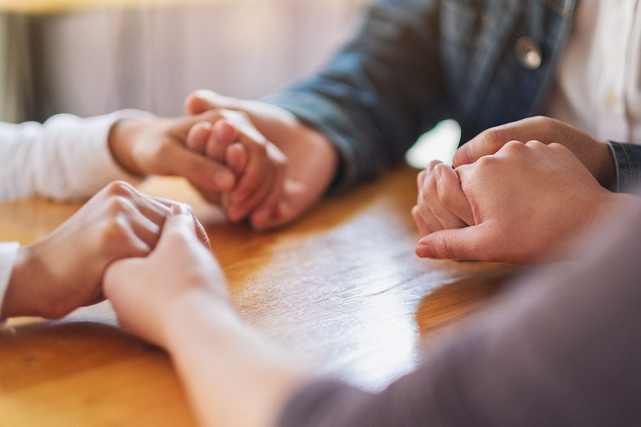 Residential Drug Treatment Center Insurance - Group of Patients Holding Hands During a Treatment Session