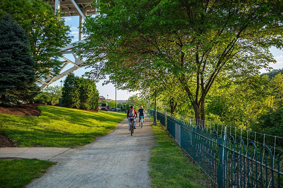 About Our Agency - Beautiful Green Biking Path Cutting Under a Steel Bridge, a Fence to the Right