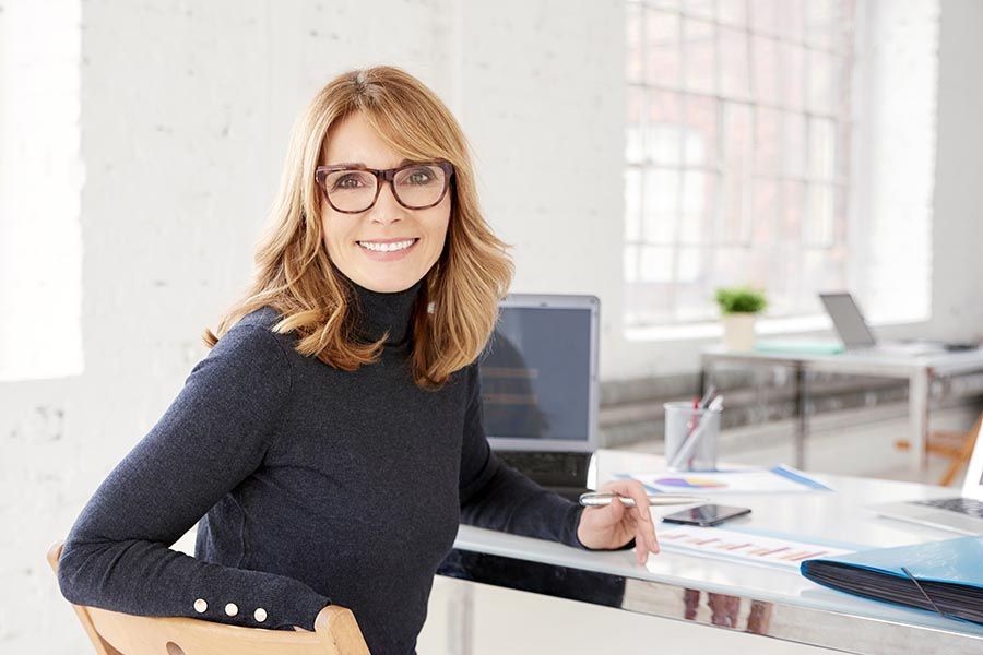 Business Insurance - Businesswoman in Glasses and Black Turtleneck at a Desk in a Bright Office