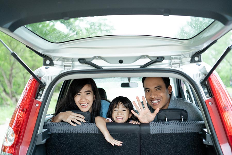 Client Center - Family Peeking Out the Back of Their Hatchback Car on a Sunny Tree-Lined Street