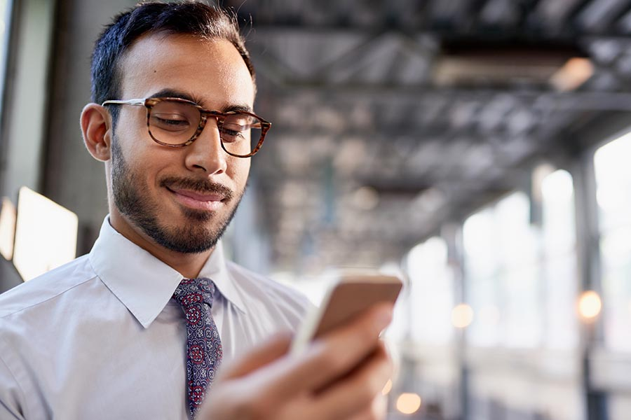 Contact - Young Businessman With Glasses and Beard Looking at His Phone in a Train Station