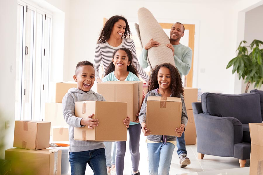 Personal Insurance - Family Moves in to Their New Home, Kids Carrying Boxes and Running Ahead, Everyone Smiling