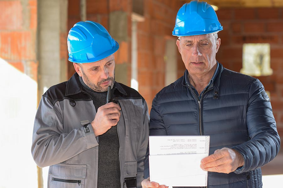 Specialized Business Insurance - Two Contractors Consulting on a Job, Wearing Blue Hardhats
