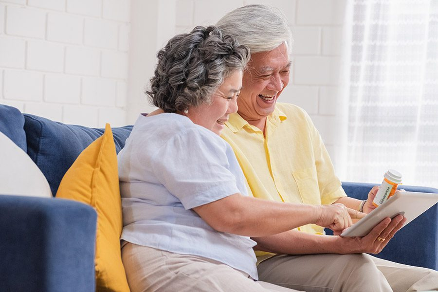 Medicare Part D Plan - Couple Use a Tablet to Video Conference with Their Doctor about Prescription While Sitting on Sofa at Home