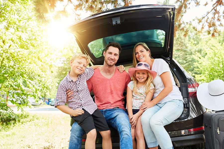 About Our Agency - Family Sits in the Back of Their Car, Dressed for a Sunny Summer Day