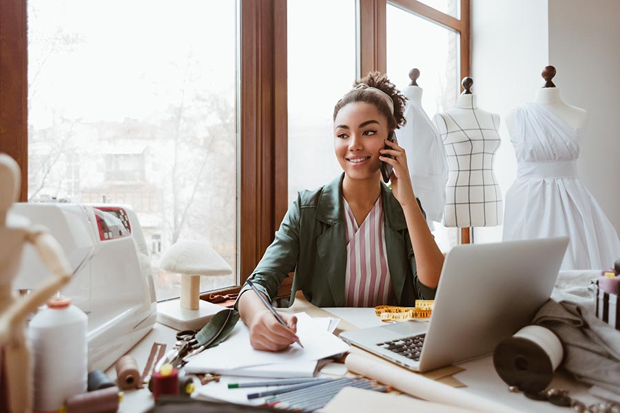 Business Insurance - Small Business Owner Makes a Call at Her Desk With Dressforms and Sewing Supplies Around Her