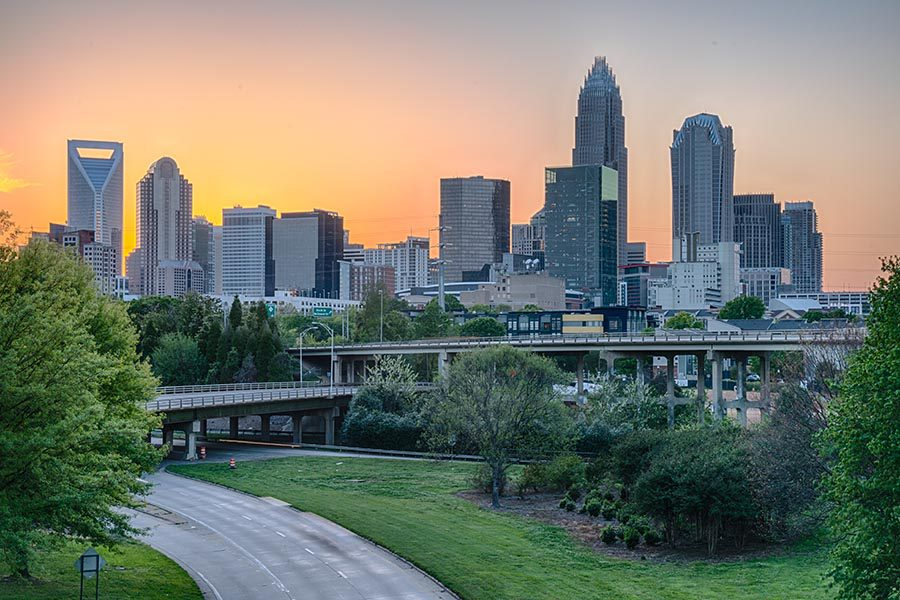 Contact - City of Charlotte, NC Skyline With a Sunset Behind the High Rises, a Green Park in the Foreground