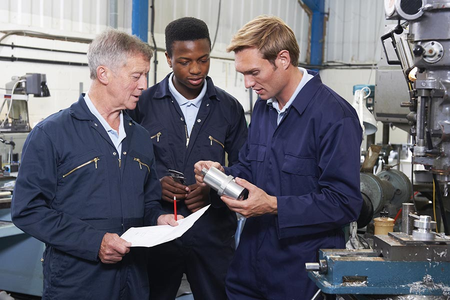 Safety and Loss Control - Three Technicians in Blue Coveralls Consult Over a Piece of Equipment in a Machine Shop