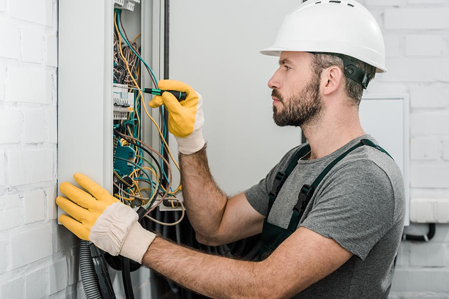 Specialized Business Insurance - Electrician Works in a White Hardhat and Gloves