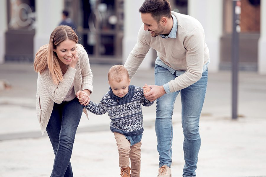 About Our Agency - Young Father and Mother Helping Their Baby to Walk in the City Street
