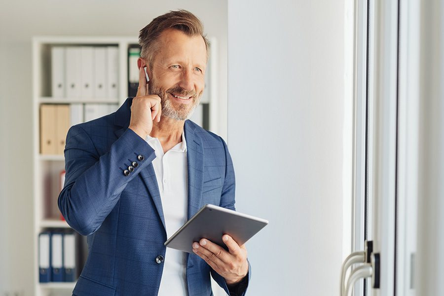Business Insurance - Business Owner Talking on Cell Phone While Holding Tablet in His Office