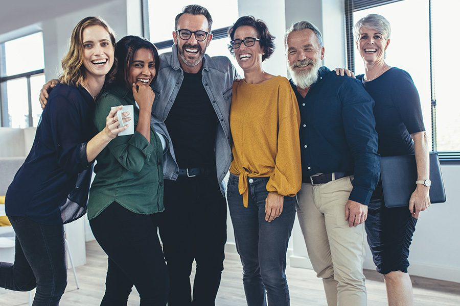 Employee Benefits - Cheerful Business Professionals Posing for a Portrait and Laughing in a Modern Office