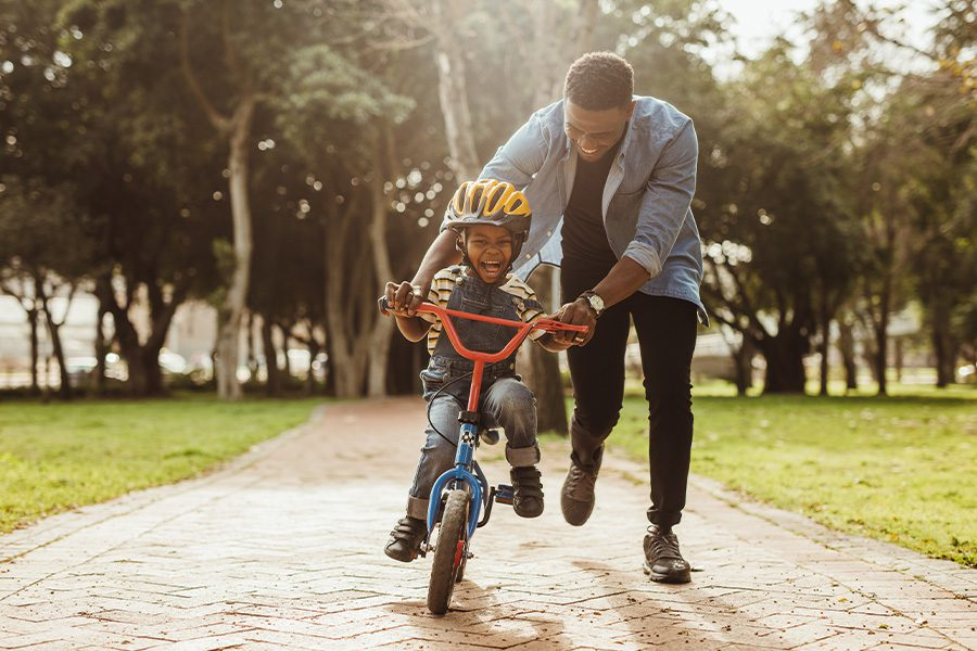 Northwood, OH - Father Teaching His Son How to Ride a Bike at the Park
