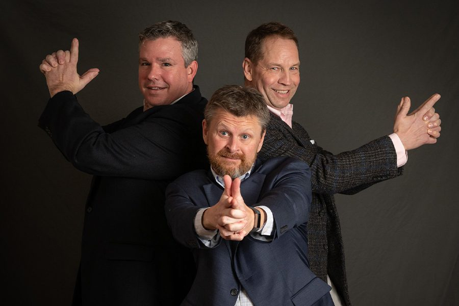 Meet the Team - Agency Owners Portrait in a Funny Stance Acting Like They Are Holding Guns