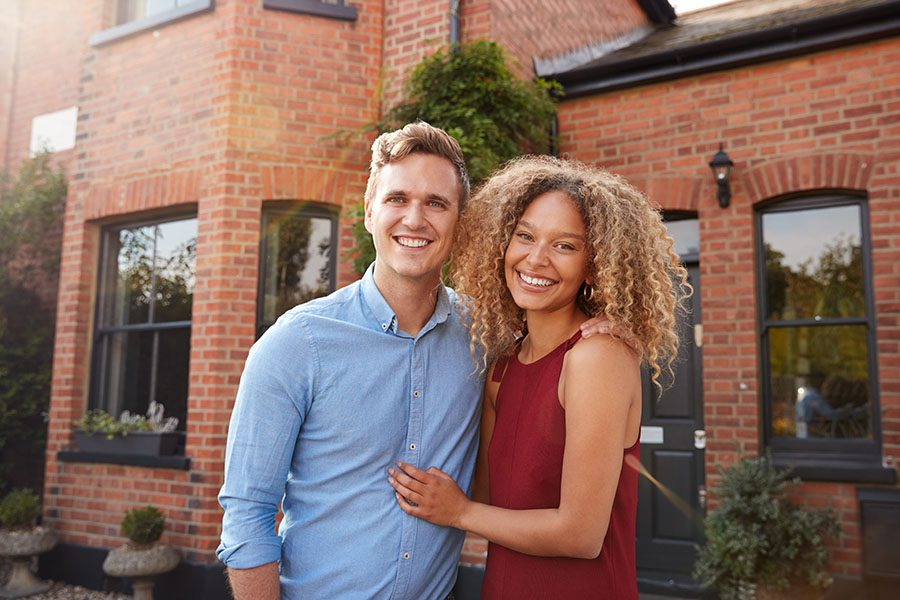 Personal Insurance - Portrait of Excited Young Couple Standing outside of Their New Home Together