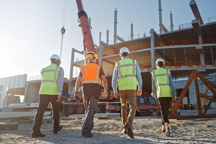 Specialized Business Insurance - Team of Specialists at an Industrial Building Construction Site with a Crane in the Background
