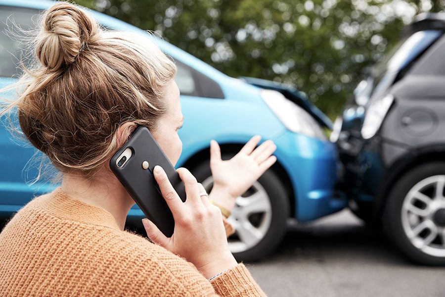 In Case of Emergency - Female Motorist Involved in a Car Accident and Calling Her Insurance Company for Recovery Service