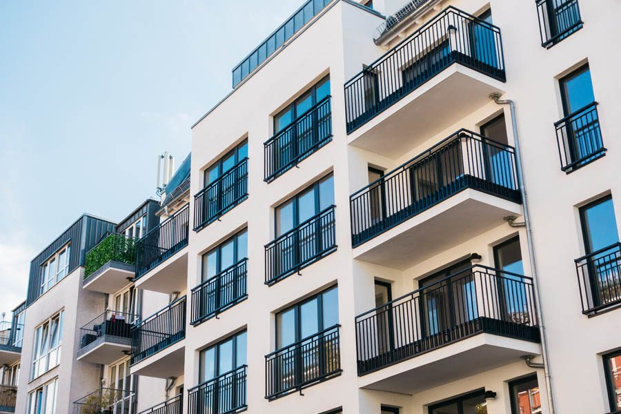 Multifamily Property Insurance - Newer Three Story Apartment Building Against a Blue Sky
