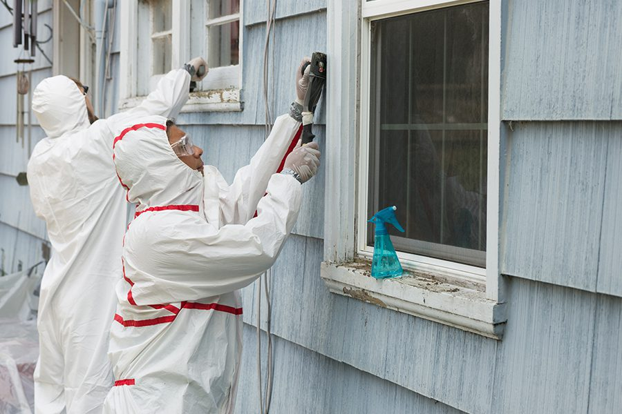 Abatement Contractor Insurance - Workers in Protective Gear While Removing Hazardous Materials From the Outside of Home