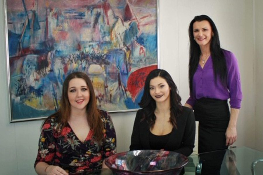 About Our Agency - Arica, Emily and Shyenne Sitting and Standing Together Near an Abstract Painting