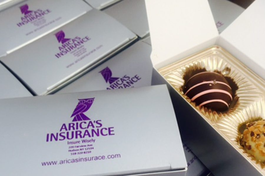Blog - Display of Single Serve Boxes of Chocolate Covered Strawberries With Arica's Insurance Logo on Them