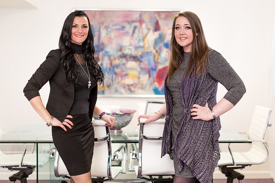 Business Insurance - Arica and Emily Standing in Conference Room With an Abstract Painting Behind Them
