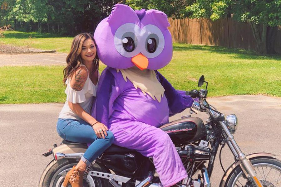 Contact - Arica and the Company Mascot, Athena Riding a Motorcycle on A Sunny Day