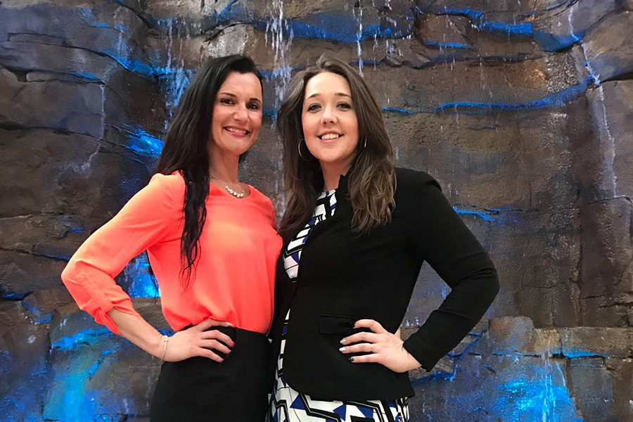 Employee Benefits - Arica and Emily Standing in Front of a Stone Waterfall With a Blue Lighting Display
