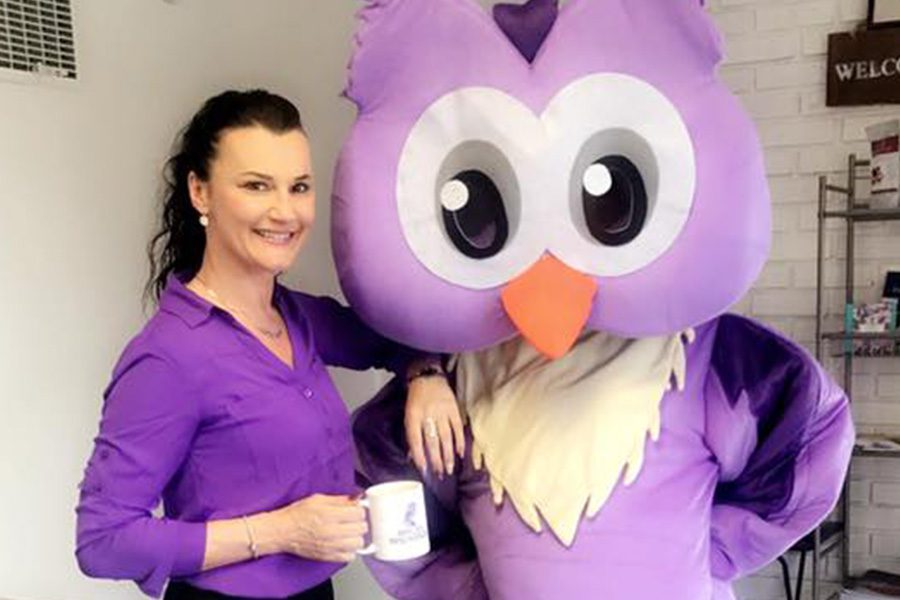 Notary Services - Arica Standing With Company Mascot, Athen While Holding a Cup