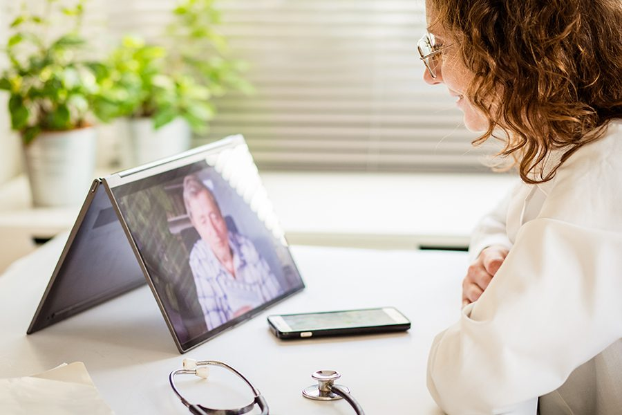 Individual Telemedicine - Doctor Diagnosing Patient Over Video Conference with Tablet in the Office