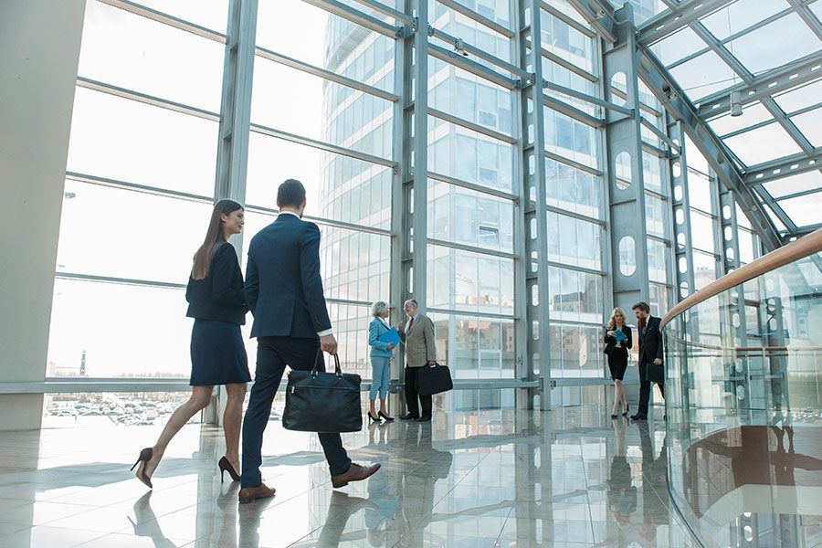 Business Insurance - Business Colleagues Walking along a Large Glass Windows in a Modern Office Building