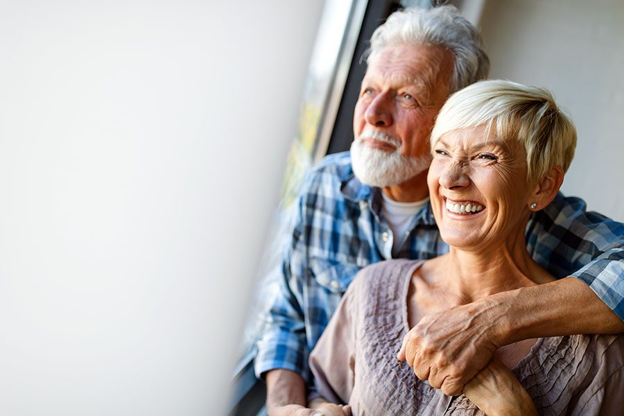 Medicare - Happy Senior Couple Hugging and Laughing While Looking Out the Window of Their Home