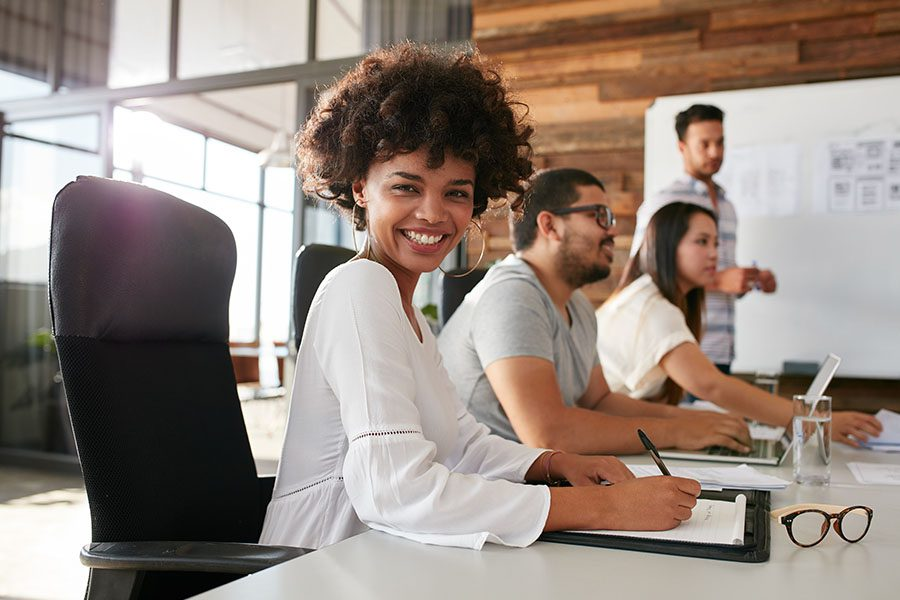 Specialized Business Insurance - Smiling Woman Looking at Camera and Sitting during a Business Presentation in a Large Conference Room of a Modern Office