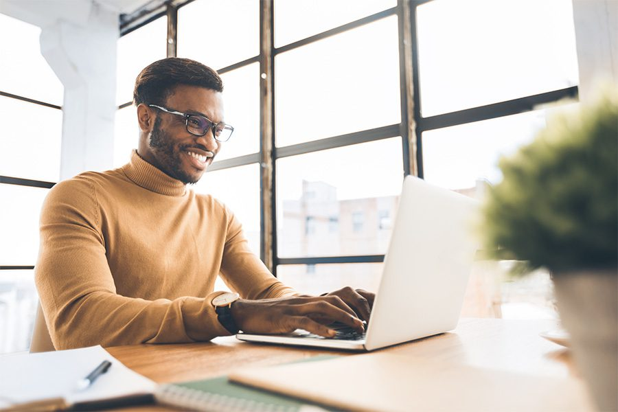 Blog - Man Smiling and Working in the Office While Typing on A Laptop