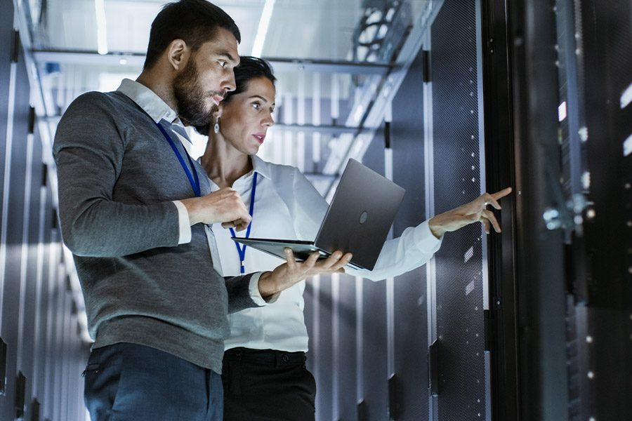 IT Contractor Insurance - IT Specialist Holding a Laptop in a Data Center with Colleague