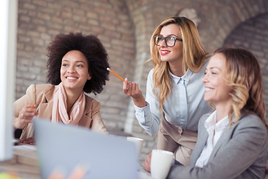 Business Insurance - Group of Young Woman Working Together During a Meeting In Their Office With a Brick Wall Background