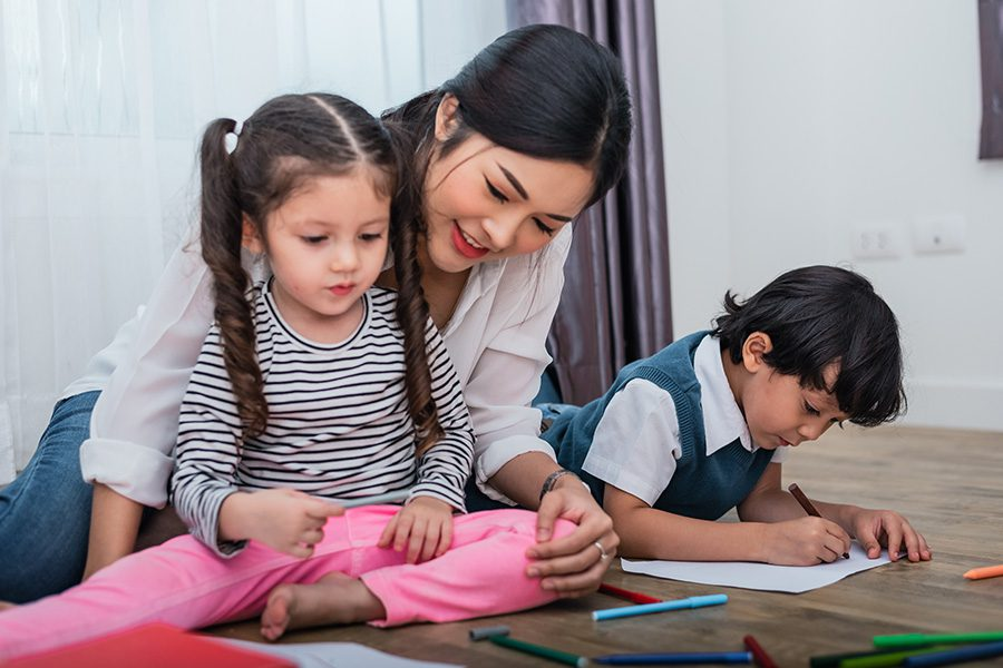 Personal Insurance - Daughter and Son Painting With Colorful Crayon Color in Home With Their Mother