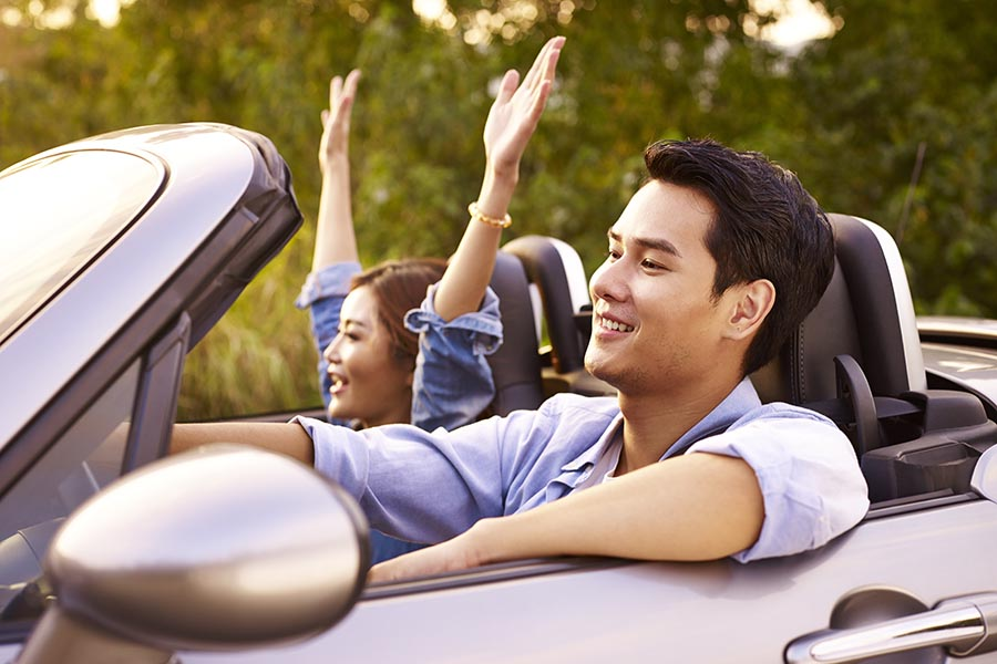 Client Center - Couple Cruises in a Convertible, Wife Cheering With Hands in the Air, Husband Smiling With His Arm Leaning on the Door