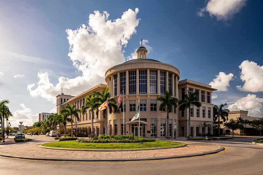 Doral, FL Insurance - City Hall Of Doral, Florida, A Large Stone Building With a Round Facade, Flags, Palm Trees, and a Round Brick Driveway