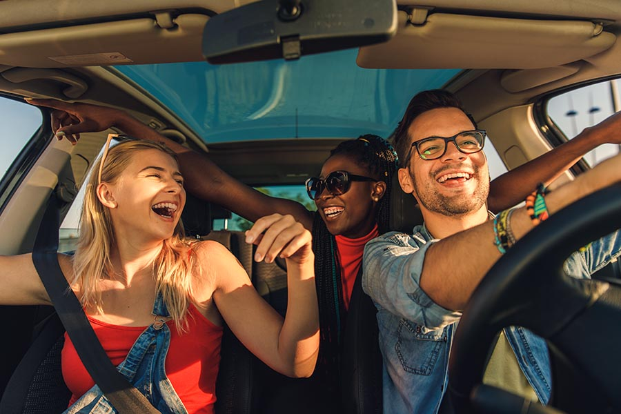 About Our Agency - Friends Sing and Laugh in Their Car on a Sunny Day, Dressed for Summer