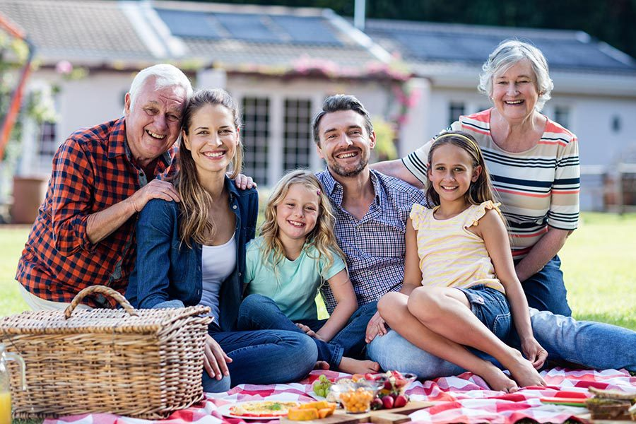 Personal Insurance - Three Generations Smile and Sit on a Picnic Blanket, a Picnic Basket and Plates of Food Spread Out, a Lovely Home Behind the Family