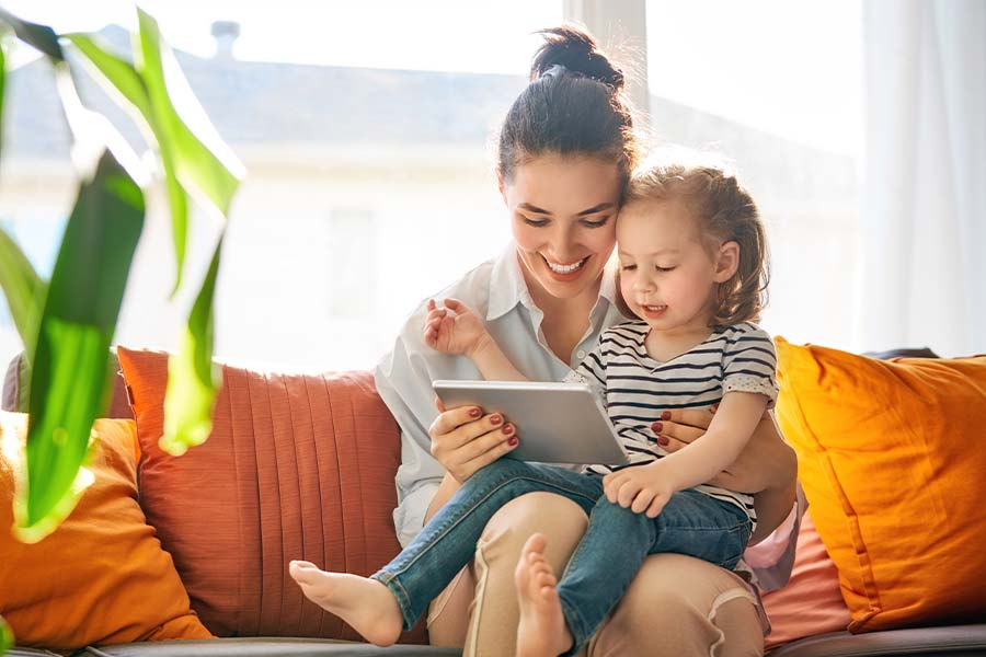 Client Center - Smiling Mother and Child Sitting Together on the Sofa in Living Room with a Tablet on a Sunny Day